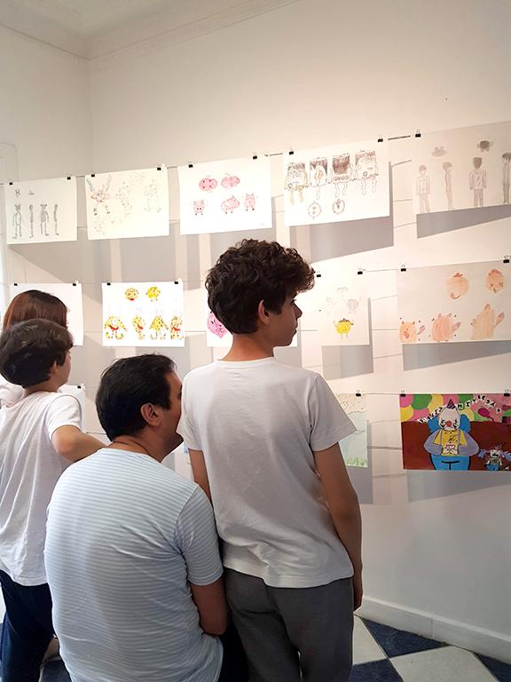 Exposição Arte para Crianças pais e crianças olham desenhos